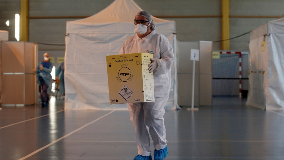 A medical worker is shown wearing a full protective suit and face mask and carrying a box of medical supplies.