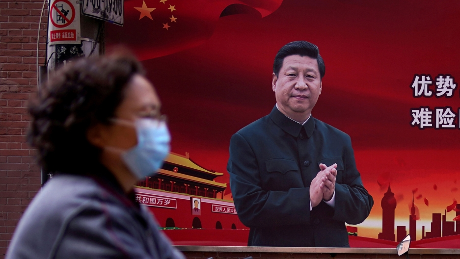 A woman is shown in soft focus and wearing a protective mask while walking past a portrait of Chinese President Xi Jinping on a red background.