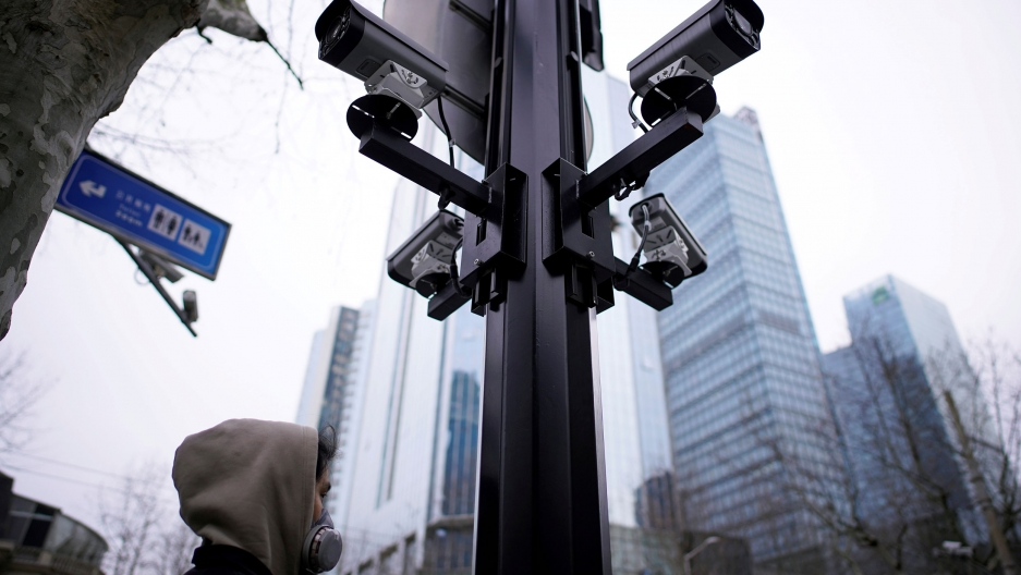 A metal poll is shown with four surveillance cameras pointed out in four separate directions as a man walks by wearing a face mask.