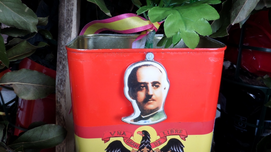 General Franco's face on the side of a red flower pot at his grave.