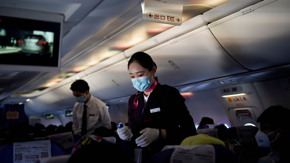 A flight attendant wearing a face mask to prevent the spread of coronavirus disease (COVID-19) takes body temperature measurements of passengers with a thermometer on a Shanghai Airlines flight in Shanghai, China, March 25, 2020.