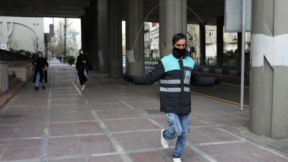 A man wearing a protective face mask and gloves, amid fear of coronavirus disease (COVID-19), jumps rope at Valiasr street in Tehran, Iran, March 26, 2020.