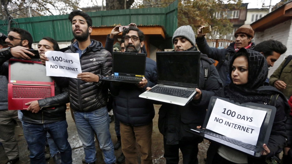 Kashmiri journalists display laptops and placards during a protest demanding restoration of internet service, in Srinagar, Nov. 12, 2019.