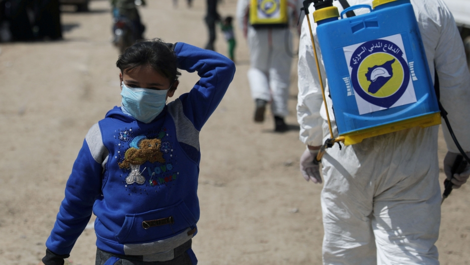 An internally displaced Syrian girl wears a face mask as members of the Syrian Civil defence sanitize the Bab al-Nour internally displaced persons camp, to prevent the spread of the coronavirus(COVID-19) in Azaz, Syria, March 26, 2020.
