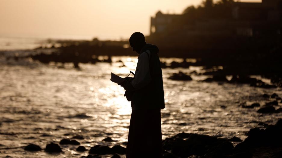 A man meditates at the beach amid the outbreak of the coronavirus disease (COVID-19), in Dakar,Senegal, March 26, 2020.