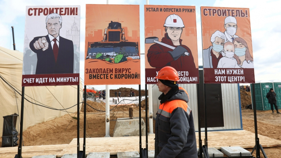 A construction worker walks past motivational placards designed in the style of Soviet propaganda posters