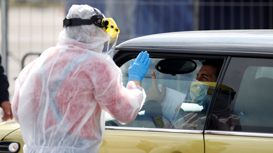 A health worker wearing a full protective gown and face guard is shown standing with his hand in the air at a drive-through coronavirus disease testing center.