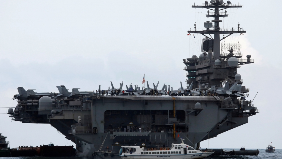 The USS Theodore Roosevelt aircraft carrier is shown from one end with several airplanes parked on the deck.