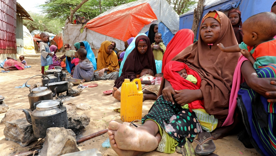 A woman and children in headscarves sit on the ground in front of tents