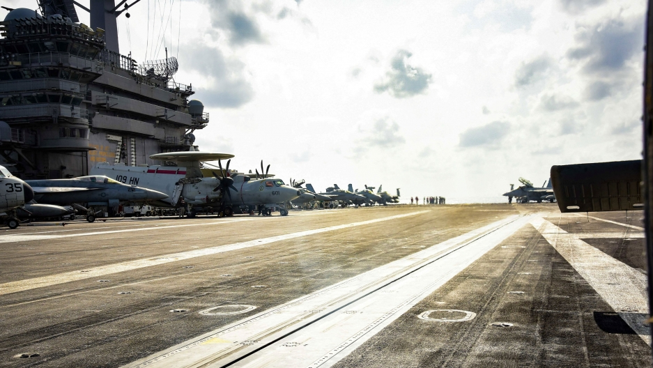 A photograph taken from the deck of the USS Theodore Roosevelt aircraft carrier with the ship's tower and several airplanes in the background.
