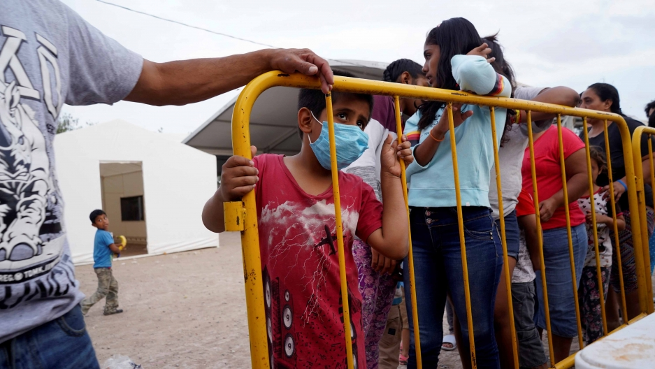 A migrant child, who is seeking asylum in the US, wears a protective mask as he stands in line for food, amid an outbreak of the coronavirus disease (COVID-19), in the migrant camp of Matamoros, Mexico, April 1, 2020.