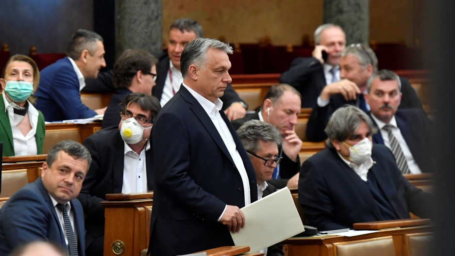 Hungarian Prime Minister Viktor Orban is shown standing among lawmakers and wearing a dark suit jacket.