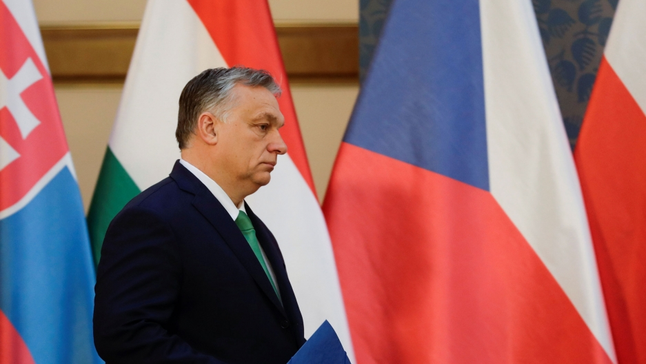 A man in a suit stands in front of European flags