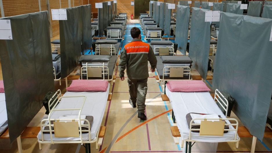 A man wearing a work uniform with an orange top walks down an aisle with several beds lining both sides.