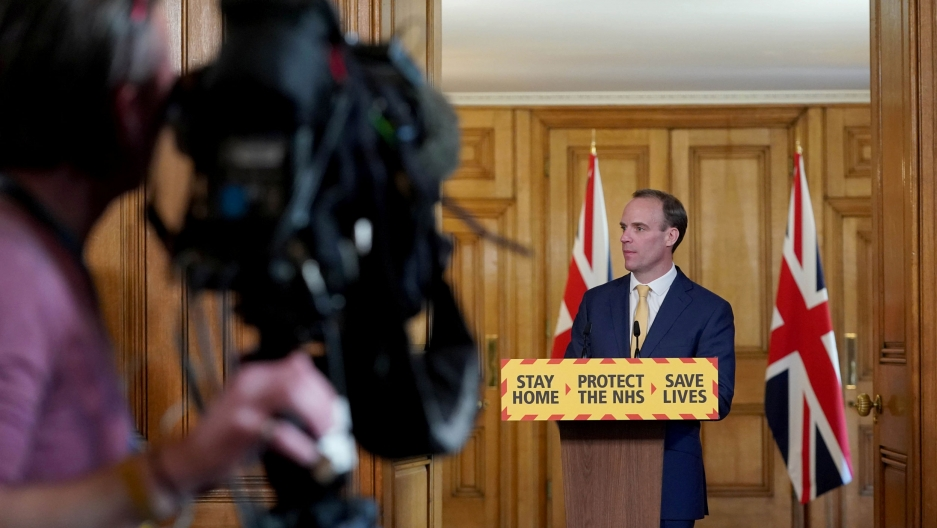 "Britain's Foreign Secretary Dominic Raab is shown standing behind a podium witth the words, ""Stay Home, Protect the NHS, Save Lives"" printed on it."