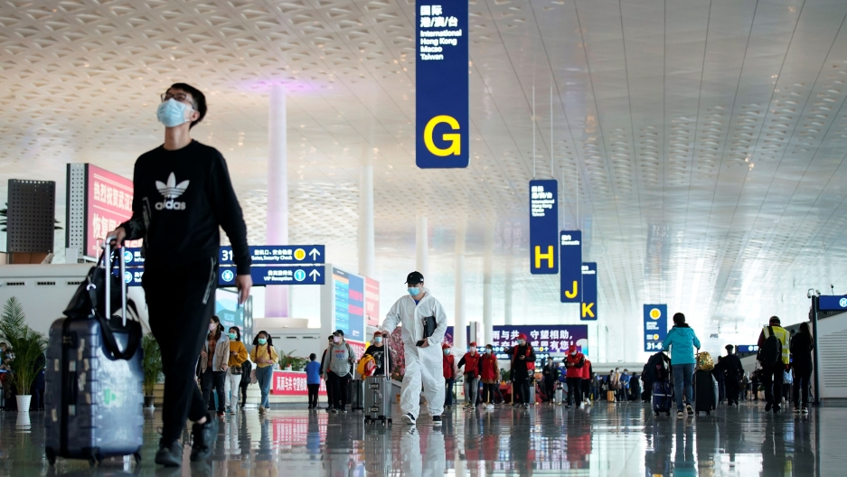 A large airport departures area is shown with several passengers walking toward gate agents.