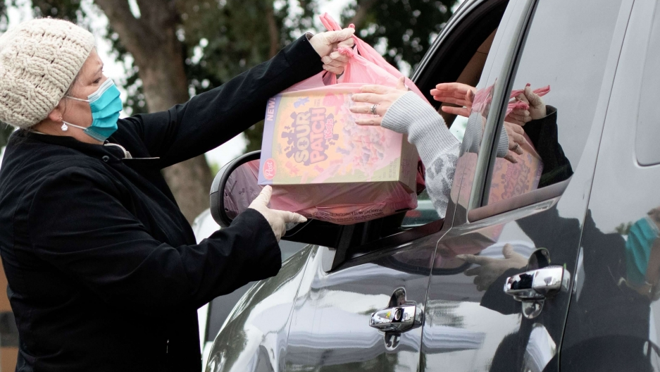 A woman with a mask hands a pink plastic bag to a woman in a car