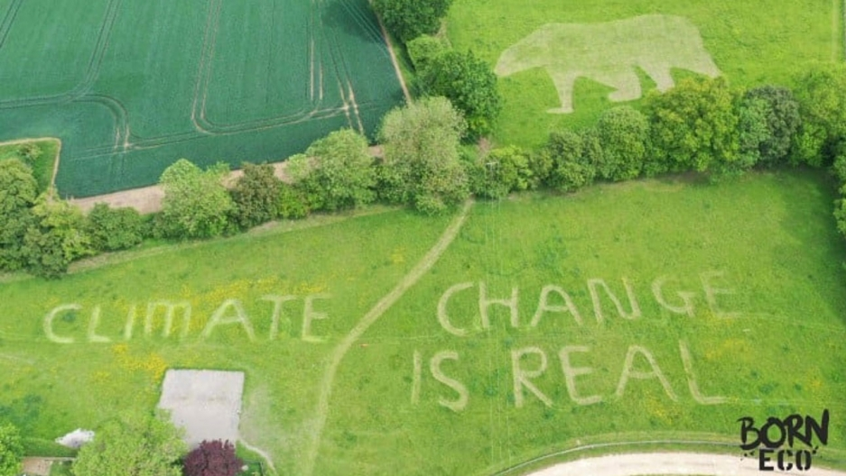 "An aerial view of a field with the message ""Climate change is real"""