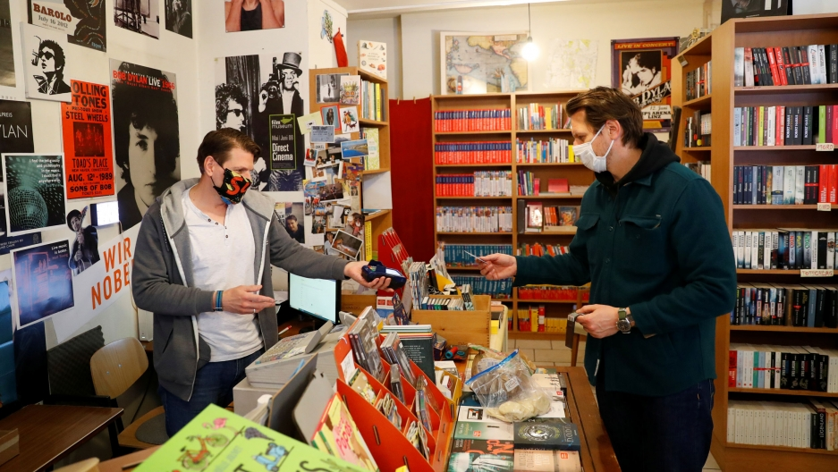 A man holds a card reader as another pays for a purchase in store with books and music posters.