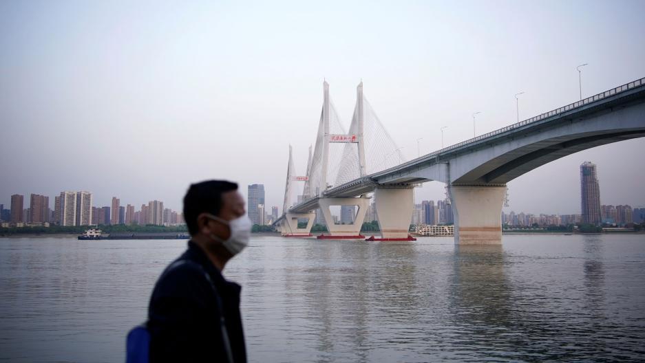 A man wearing a face mask is seen under a bridge of Yangtze river