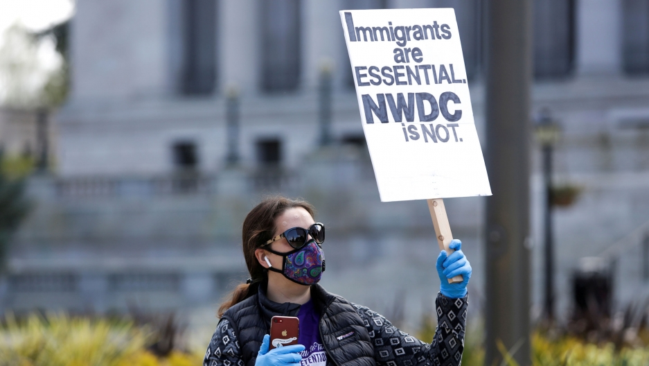 "A woman in a mask and gloves holds a sign reading ""immigrants are essential NWDC is not"""