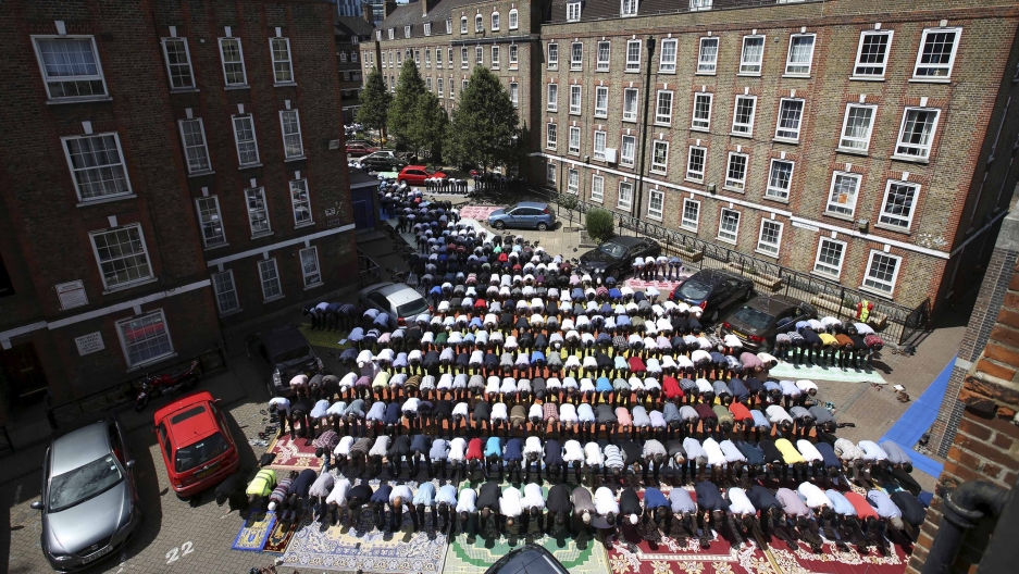 An aerial Muslims attend Friday prayers in the courtyard of a housing estate next to the small BBC community center and mosque in east London, Britain, July 10, 2015.