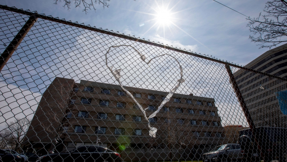 A chain-link fence is shown with a clothe heart woven into it and a brick building in the background.