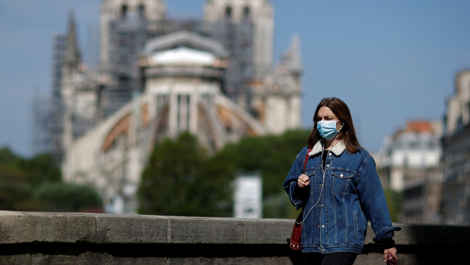 A woman, wearing a protective face mask and a jean jacket is shown walking past Notre-Dame Cathedral in the background in soft focus.