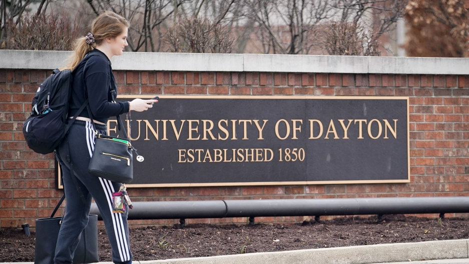 A student carries her bags in front of a sign for the University of Dayton