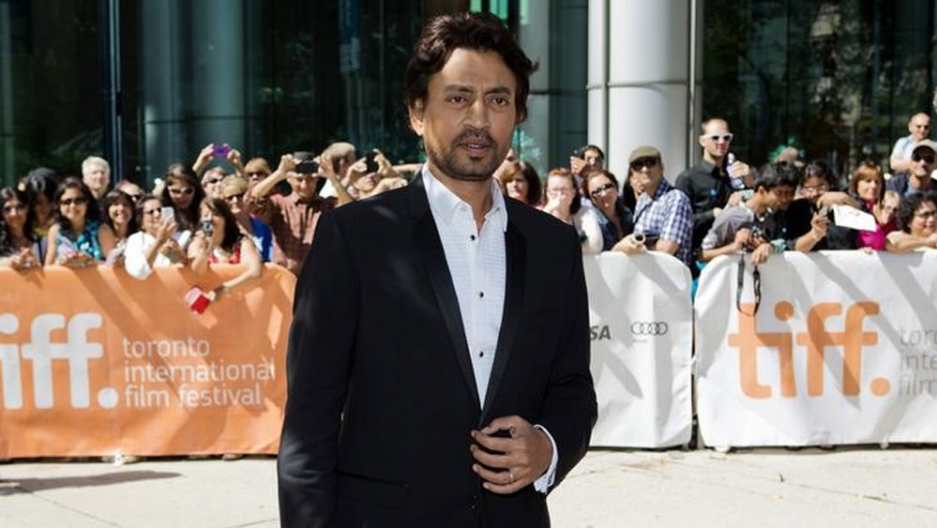 Indian actor Irrfan Khan is shown wearing a dark tuxedo with a crowd in the background.