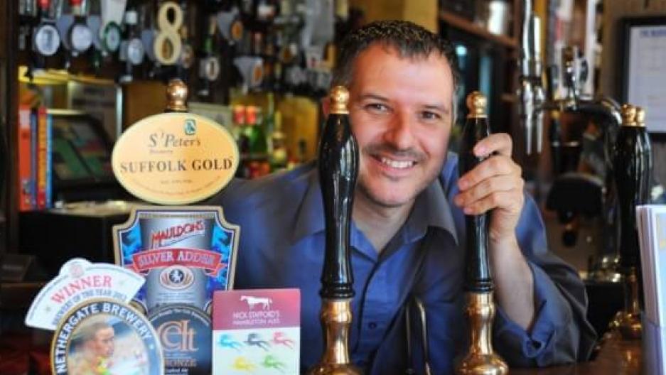 A man poses behind taps at the bar