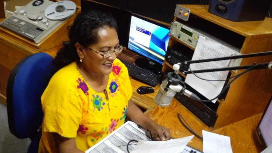 A woman wears a bright yellow blouse and sits in a radio studio