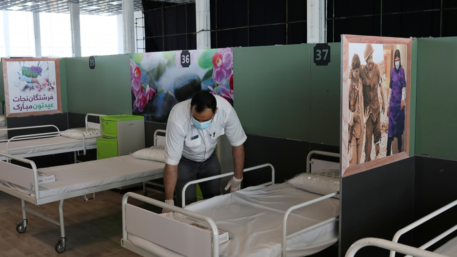 A man makes a bed in a row of beds with medical posters on the dividing walls