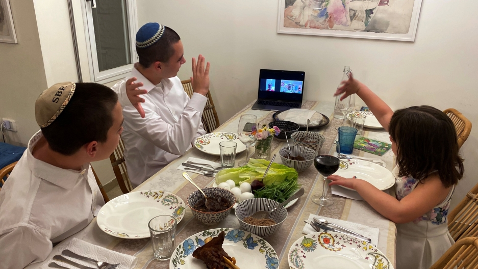 Three siblings in Mevasseret Zion, near Jerusalem, wave to their their grandmother in Haifa as she joins their PassoverSedervia Zoom application as Israel takes stringent steps to contain the coronavirus (COVID-19) April 8, 2020.