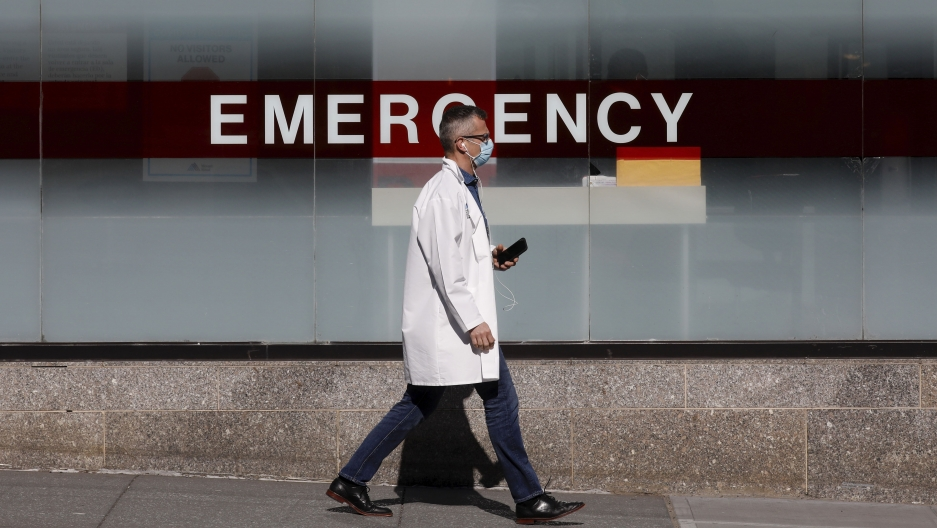 A doctor wears a protective mask as he walks outside Mount Sinai Hospital in Manhattan during the outbreak of thecoronavirusdisease (COVID-19) in New York, April 1, 2020.