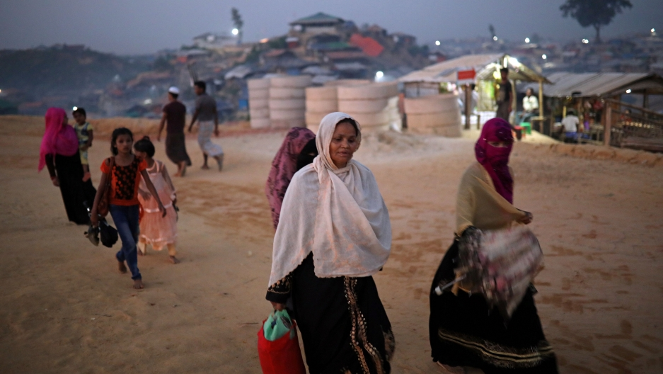Rohingya refugees walk along the road in the evening at Balukhali camp in Cox's Bazar, Bangladesh, Nov. 16, 2018.