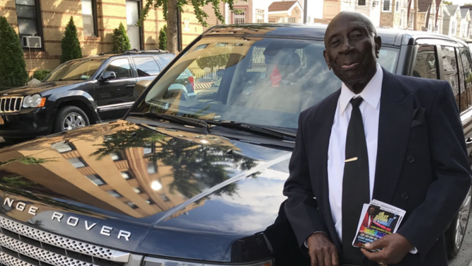 A Black man in a suit stands by a Range Rover holding a book