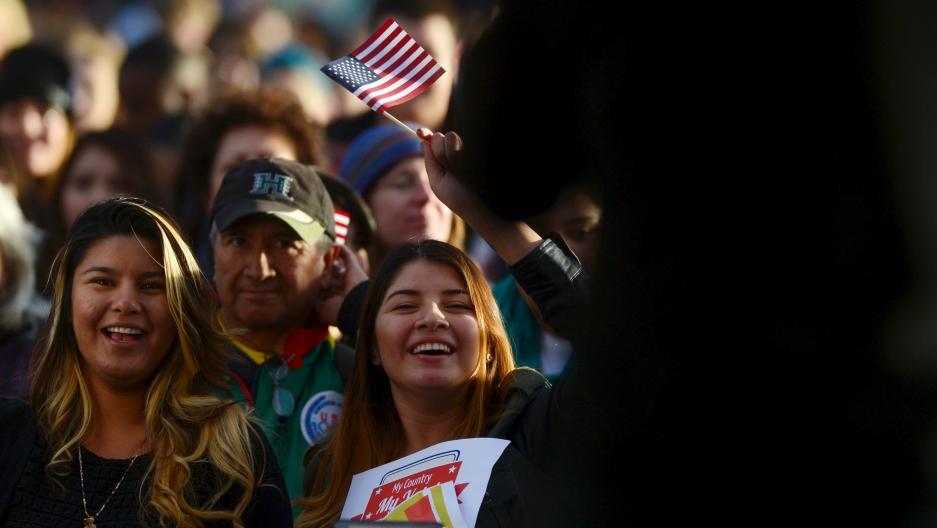 Un grupo de mujeres sonrien y miran a un politico hablar.