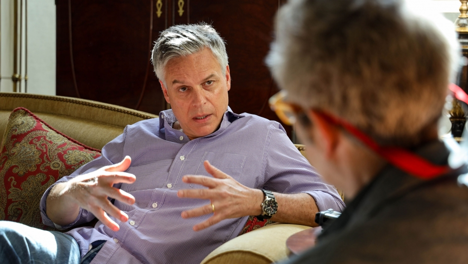Ambassador Jon Huntsman Jr. is shown in a button down shirt sitting across from Marco Werman who is wearing glasses.