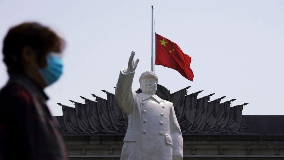 A person wearing a protective face mask is shown in soft focus walking past a statue of late Chinese chairman Mao Zedong with the red Chinese flag flying.