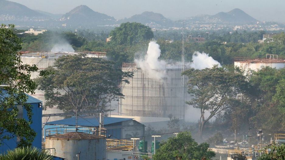 A photo taken from a distance shows the LG Polymers plant with several large towers releasing smoke.