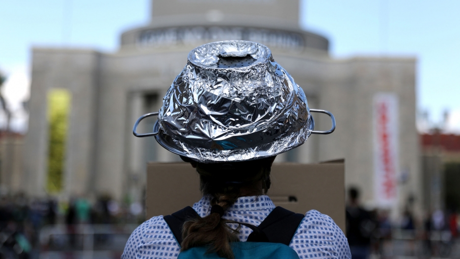 A woman is shown in a photograph from behind wearing a tin-foil hat.