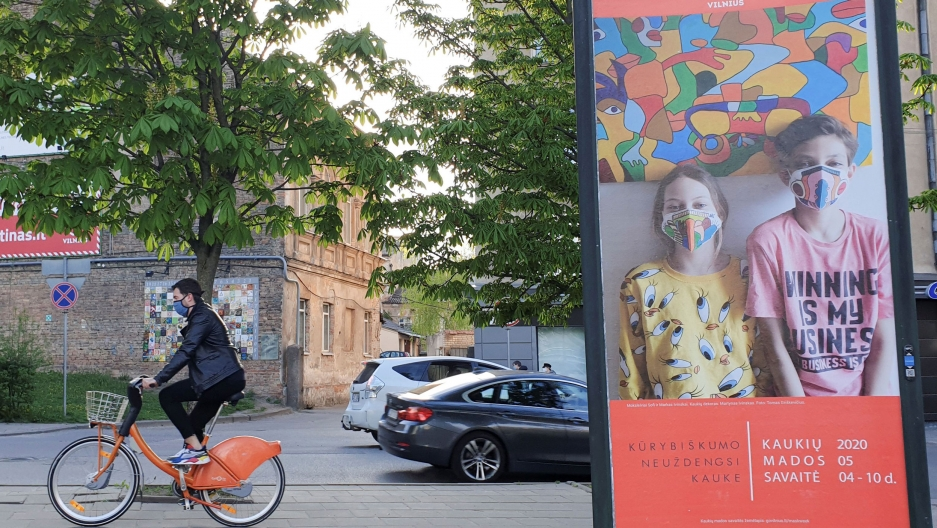A person on an orange bicycle rides past a billboard of people with masks
