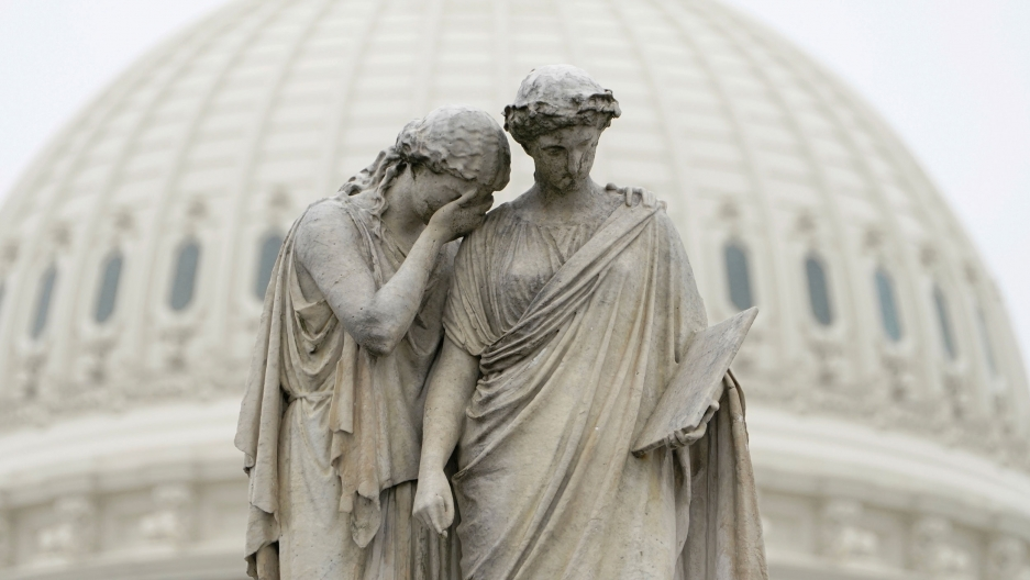 A statue is shown depicting two women with one holding her hand to her face and the other holding a book.