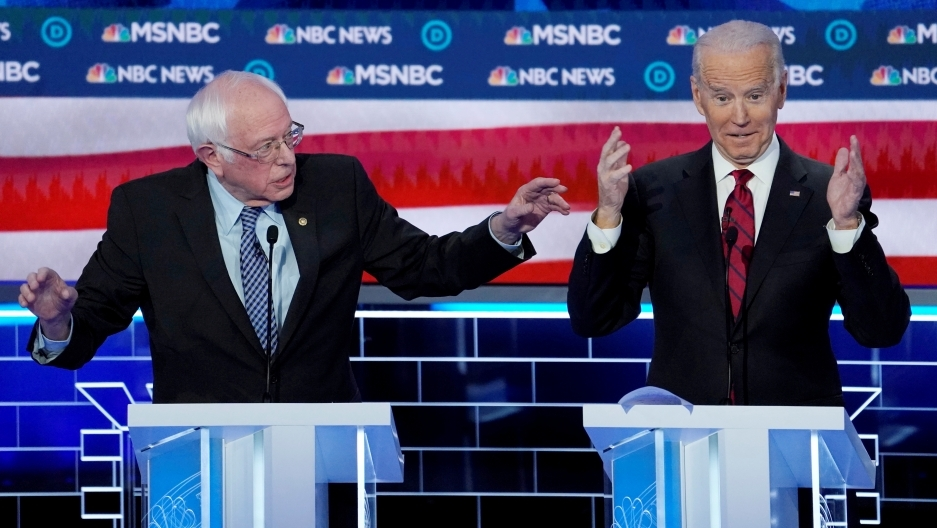 Joe Biden y Bernie Sanders speak at a debate.