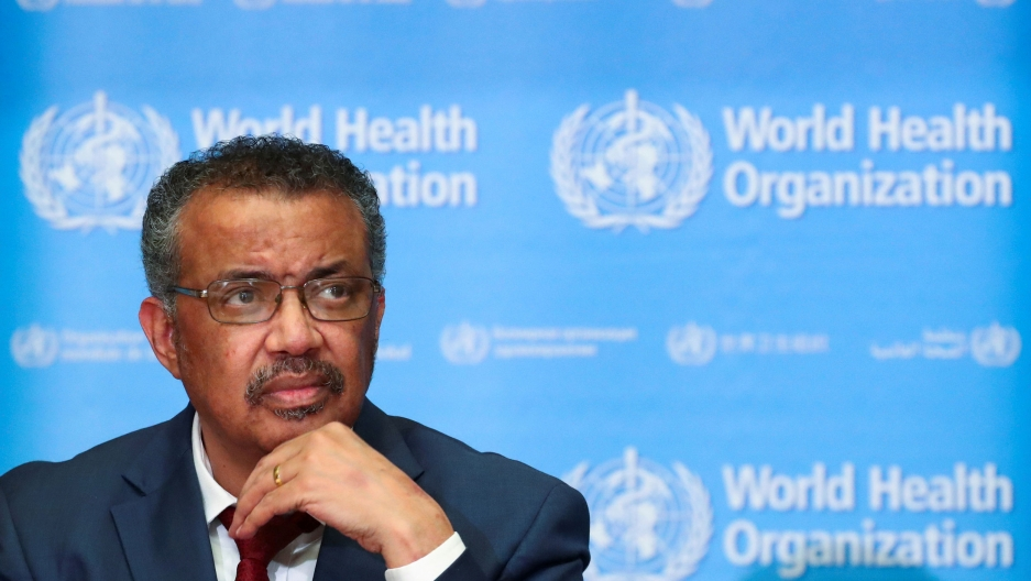 Tedros Adhanom Ghebreyesus is shown sitting with a red tied and jacket with his hand on his chin.