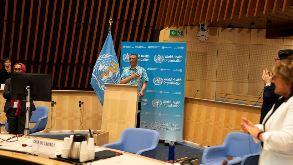 Tedros Adhanom Ghebreyesus is shown standing at a wooden podium with the blue WHO flag next to him and wearing a blue-print button down short-sleeved shirt.