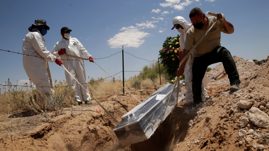 For men are shown wearing protective clothing and lowering a casket wrapped in clear plastic into a grave.