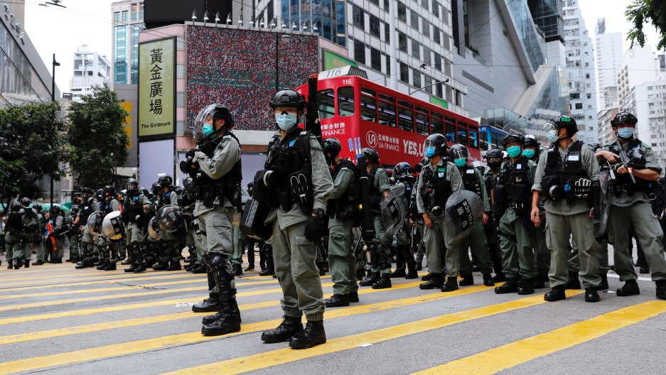 Riot police are shown standing in a line across the middle of a large street and wearing protective armor in Hong Kong.