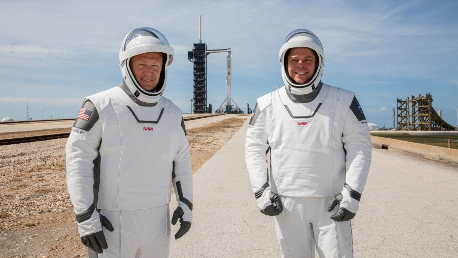 Two NASA astronauts in spacesuits in front of a rocket launch pad